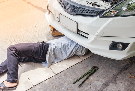 garage: Mechanic in uniform lying down and working under car at auto service garage, Repairing a car concept Stock Photo