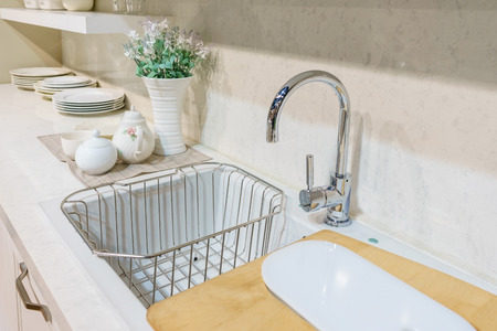 sink: Modern kitchen furniture with contemporary kitchenware like faucet and sink in house. Stock Photo