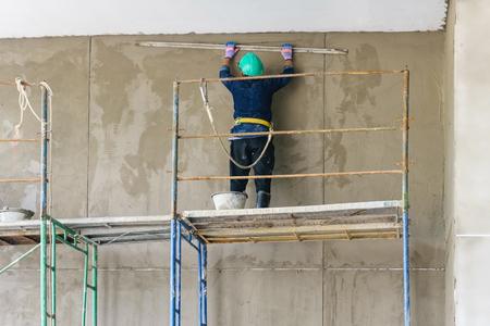 fabrieksarbeider met pleisterwerk gereedschappen die een huis renoveren. bouwvakker pleisterwerk gevel industrieel gebouw met leveller Stockfoto