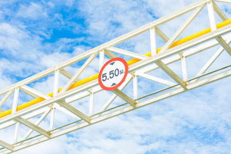 building regulations: Height Restriction limit Sign on pipe rack, white metal sign on steel structure with blue sky