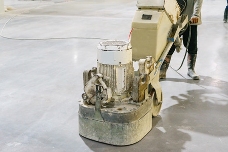 Vrouwenarbeider die oppoetsende machine gebruikt om oppervlakte glad te maken om betonplak te beëindigen. Betonnen vloeren Stockfoto