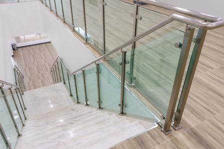 鋼鉄およびガラス手すりの新しいモダンな建物とモダンな白い大理石の階段。