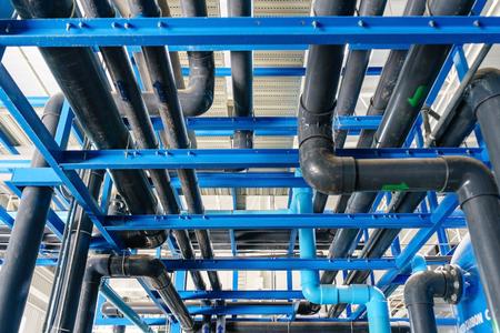 대형 산업용 수처리 및 보일러 실. 반짝이 철강 금속 파이프와 파란색 펌프 및 밸브입니다.