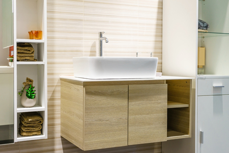 modern bathroom interior in foreground of counter top washbasin in a contemporary style using natural materials.