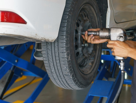 impact wrench: Professional car mechanic changing car wheel in auto repair service.