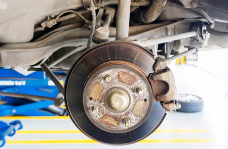 rusty car: Closeup disc brake of the vehicle for repair, in process of new tire replacement. Car brake repairing in garage