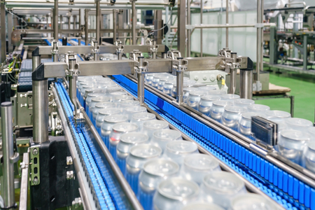 Pakowane puszki na przenośniku taśmowym w średniej fabryce