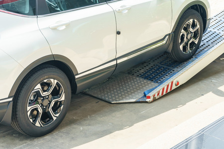 A broken vehicle strapped down to the platform of flat bed tow truck. Roadside service Stock Photo