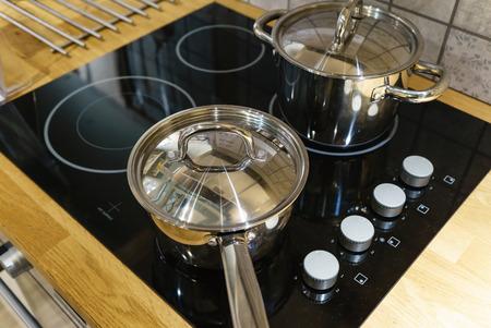 Metal Pot en la placa de inducción en la cocina moderna. cocina moderna olla cocina inducción eléctrica estufa encimera concepto