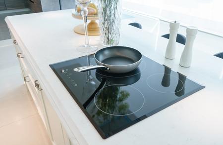 Sartén en moderna estufa de inducción negra, cocina, encimera o estufa incorporada con encimera de cerámica en el interior de la cocina blanca