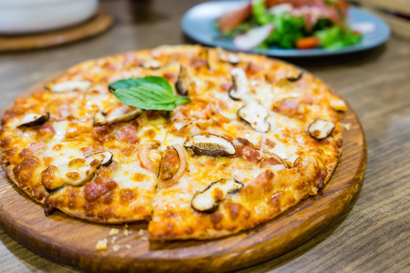 Italian fast food. Delicious hot pizza sliced and served on wooden platter with Mushroom pizza and Bacon, close up view. Menu photo.