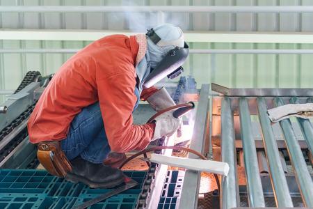 防護服を着た男性労働者は、鉄骨構造を溶接し、職人、工場技術で技術鋼工業用鋼溶接機を建て。