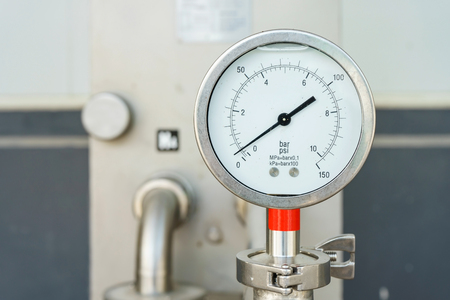 Closeup of manometer, measuring gas pressure. Pipes and valves at industrial plant.