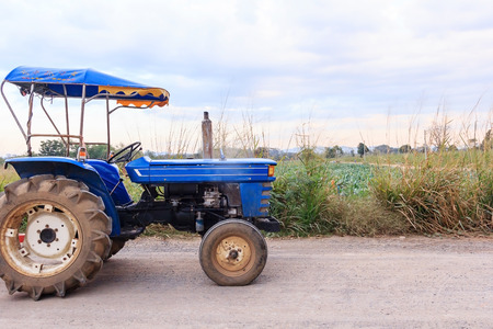 E-taen vehicle or farm tractor in countryside with green organic vegetable farm scenery, Agricultural vehicles