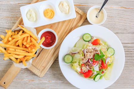french fries and ketchup on a wooden plate and Salad with fresh vegetables and tuna, Top view with Free space for your text. Stock Photo