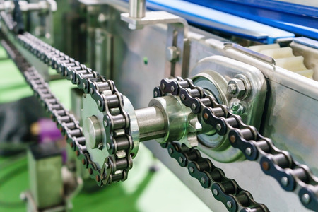 Gear and chain drive shaft in conveyor chain, and conveyor belt is on production line.