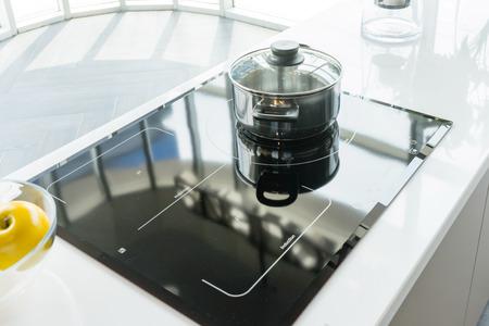 Primo piano del vaso e della pentola di cottura dell'acciaio inossidabile sulla fresa di induzione in cucina moderna. concetto moderno del piano cottura della stufa elettrica di induzione di cottura del vaso da cucina Archivio Fotografico - 97110665