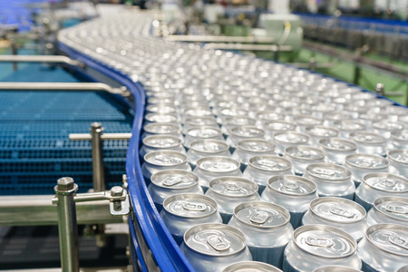 Conveyor line carrying thousands aluminum beverage cans at factory. Concept of industrial growth.