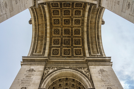 Paris Arc de Triomphe (Triumphal Arch) in Chaps Elysees at cloudy sky, Paris, France. Architecture and landmarks of Paris