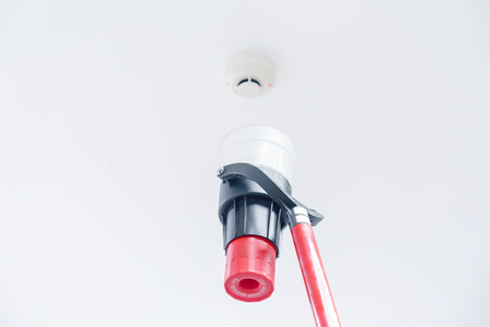 Automatic smoke detector fire alarm head on the ceiling. The smoke detector is triggered by a trickle of dum, the red indicator lights up Фото со стока