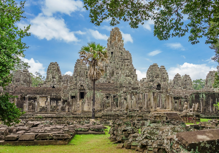 Ancient temple Bayon Angkor complex with stone faces of buddha Siem Reap on blue sky cloudy, Cambodia