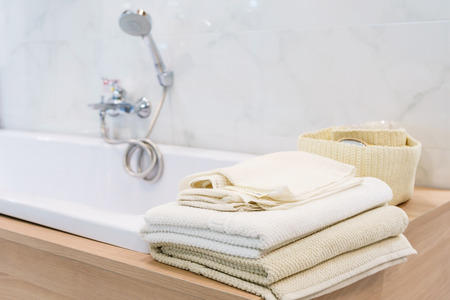 White towel lies on bathtab in bathroom in the background