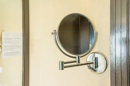 Shaving mirror sliding in bathroom with big building reflection in mirror.