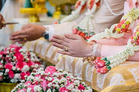 Watering ceremony for prosperity Thai wedding. The elder is pouring water and blessing the married couple to be happy. Conch shell decorated with gold. Inside the water And poured on the brides hand.
