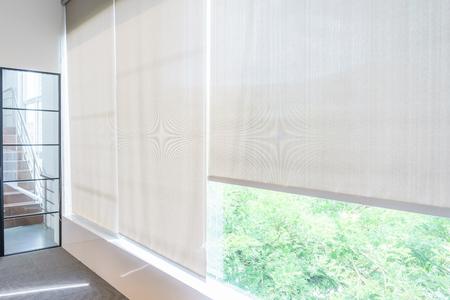 Persianas enrollables en las ventanas, el sol no penetra en la casa. Ventana en el interior de las persianas enrollables. Hermosas persianas en la ventana