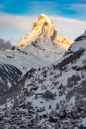 The sun shines on the tip of the Matterhorn in the Swiss Alps just before sunrise in the village of Zermatt, Switzerland. Landscape image of Matterhorn.