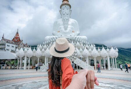 Young woman traveller leading boyfriend to the view of White five Buddha statue in Wat Phra That Pha Son Kaew temple at Phetchabun, Thailand. Traveling together. Follow me