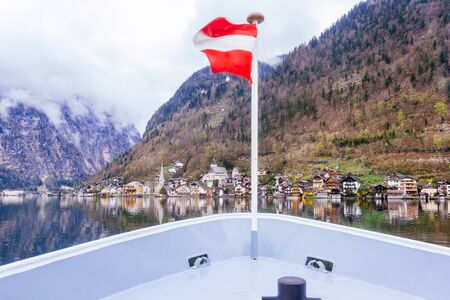Hallstatt Scenic picture-postcard view of famous mountain village by Lake Hallstatt from Approach Ferry boat with Austrian Flag in the Austrian Alps under Golden Dramatic Sky Sunset in Summer, Austria