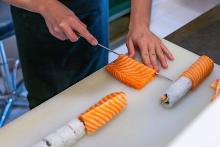 Cutting the salmon with a knife, Japanese chef making sashimi in kitchen, Sushi are made Archivio Fotografico - 129295489