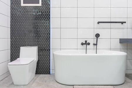 Modern bathroom interior with minimalistic shower and lighting, white toilet, sink and bathtub Archivio Fotografico - 129295406