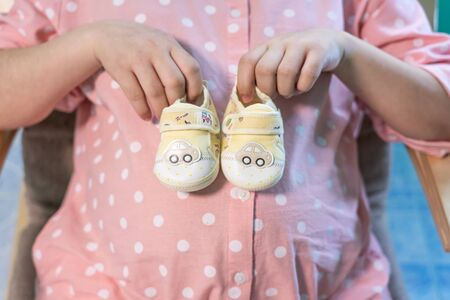Small shoes for the unborn baby in the belly of pregnant woman. Pregnant woman holding small baby shoes relaxing at home in bedroom. Small shoes for the unborn baby in the belly of pregnant woman Archivio Fotografico - 129295452
