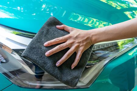 Closeup of green car cleaning with grey microfiber cloth by woman's hand in sunny day Archivio Fotografico - 131970909