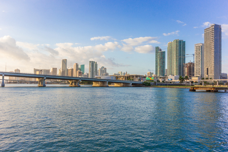 Miami city skyline panorama at blue sky cloudy with urban skyscrapers and bridge over sea with reflection