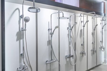 Variety of modern chrome and silver metal shower heads in the shop