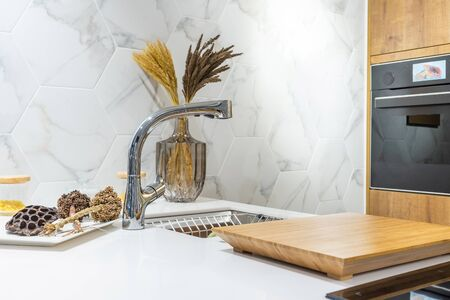 New modern faucet and kitchen room sink closeup with island and granite countertops in model house, home, apartment Archivio Fotografico - 131970421