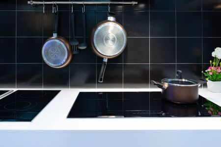Metal Pot on induction hob in modern kitchen. modern kitchen pot cooking induction electrical stove hob concept Archivio Fotografico - 131970900