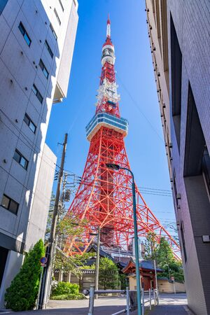 Tokyo Tower with blue sky in Tokyo. The structure is an Eiffel Tower-inspired lattice tower that is painted white and international orange to comply with air safety regulations.