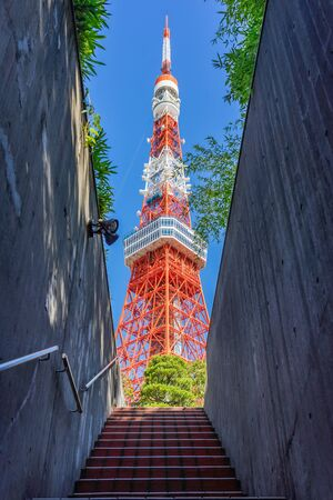 Tokyo Tower with blue sky in Tokyo. The structure is an Eiffel Tower-inspired lattice tower that is painted white and international orange to comply with air safety regulations. Archivio Fotografico - 132165317