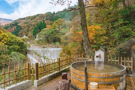 Japanese Hot Springs Onsen Natural Bath Surrounded by red-yellow leaves. In fall leaves fall in Fukushima, Japan. Archivio Fotografico - 133871356