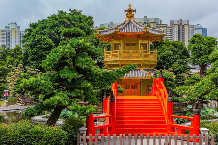 Golden pagoda of Nan Lian garden in Hong Kong city with a cloudy sky, Hongkong China Archivio Fotografico - 133859434