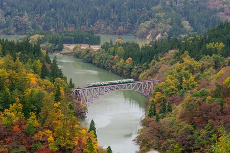Train crossing the first bridge at Tadami line with surrounding beautiful autumn foliage in Mishima ,Onuma district,Fukushima ,Japan.