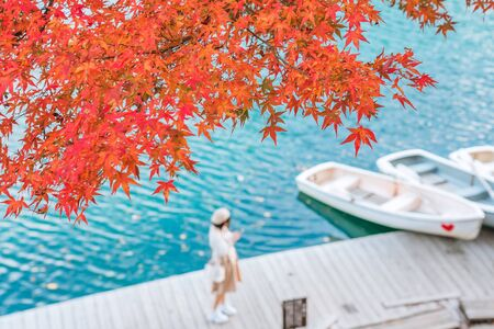 Red maple leaf on Goshikinuma or Five Colored Pond with Lover couple background, a popular destination in Highlands in autumn in Fukushima prefecture, Japan