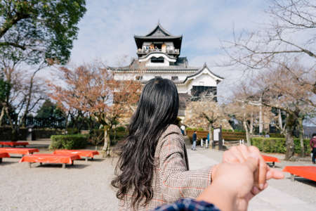 Young woman asia traveller enjoying the view of Inuyama Castle in Inuyama, Aichi Prefecture, Japan. Traveling together. Follow me