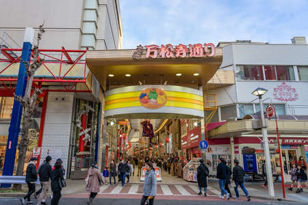 NAGOYA, JAPAN - JANUARY 18, 2020: The main red entrance gate of Osu walking street, one of the famous marketplace and shopping attractions in Nagoya City, with some tourists. Редакционное