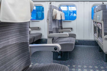 Empty interior of a passenger train car (aka coach or carriage). Rows of unoccupied seats and folding tables in economy or second class. Public transport. Фото со стока