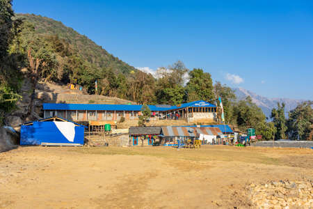 MARDI HIMAL, NEPAL - DECEMBER 30, 2019: View of Forest Camp Guest House & Restaurant on Mardi Himal trek at blue sky, Annapurna mountain range in Nepal